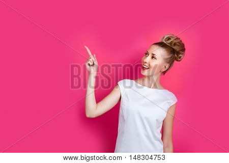 Pretty woman posing on the bright pink wall backdrop. She points finger towards