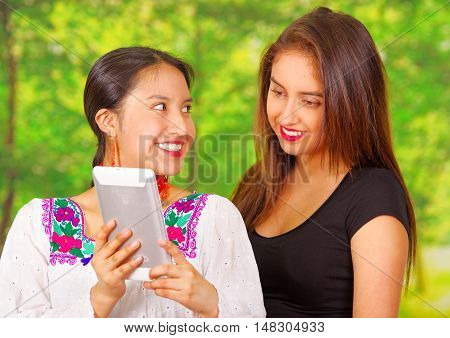 Two beautiful young women posing for camera, one wearing traditional andean clothing, the other in casual clothes, holding tablet between them interacting, both smiling, park background.