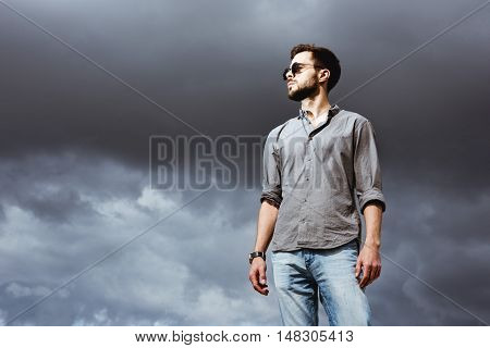 Fashion man in warm pullover posing on the cloudy sky backdrop