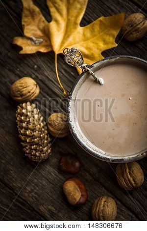 A cup of cocoa on a wooden table top view. Autumn Still Life - nuts chestnuts pine cone maple leaf