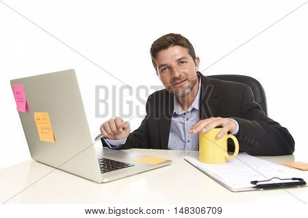 corporate portrait young attractive businessman happy and confident at office with paperwork file working on laptop computer desk smiling in success business concept isolated in white background