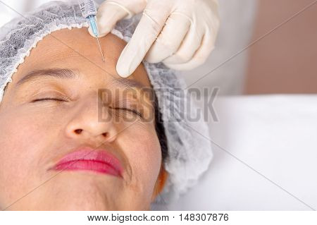 Closeup womans face receiving botox injections with syringe, cosmetic surgery concept, as seen from above.