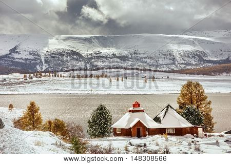 Little house on the snowy mountains background with cloudy sky