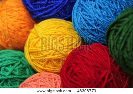 Woolen yarn balls, skeins of tangled colorful sewing threads, selective focus