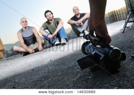 three young man siting on ground while modern video camera recording
