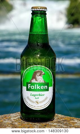 Neuhausen am Rheinfall, Switzerland - 22 June, 2016: a cold bottle of Falken bier covered by drops of water condensate on a hot day the Rhine Falls in the background. Falken bier has been brewed by the Falken brewery in the Swiss city of Schaffhausen.