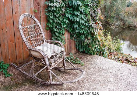 old rocking chair on the front porch of an old house. wooden wall with vine grapes
