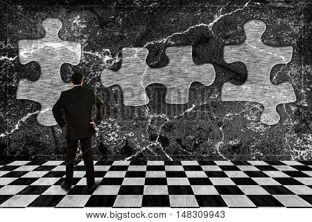 businessman staring at puzzle pieces on a grungy wall abstract concept