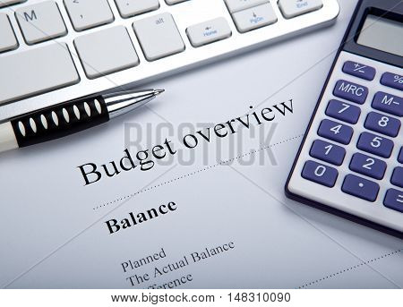 document with title budget overview and keyboard calculator close up