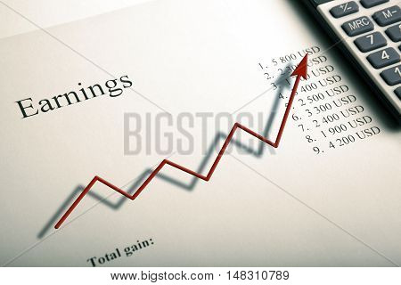 table with earnings with digits calculator and diagram close up