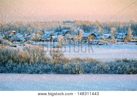 Winter rural landscape view with winter falling snow. Birds eye view of winter countryside - winter sunset landscape with winter snowfall. Winter natural rural landscape view of snowy countryside.