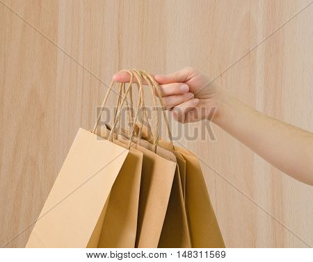 a brown kraft bag in hand on brown background