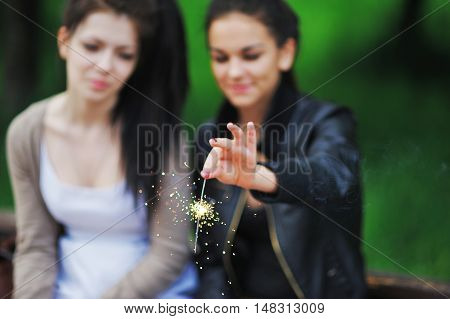 Portrait of two happy young girlfriends with long dark hair. Charming girls having fun in the park lighting candles Bengal. Blurred Background Sparkler in focus