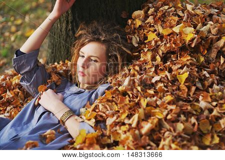 Thoughtful Beautiful Girl In A Light Purple Cloak Resting, Lying On  Pile Of Fallen Autumn Leaves In