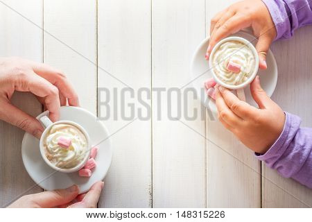 Mother and Daughters Hands with Hot Chocolate from Above on a White Wooden Table