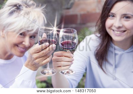 Mother And Adult Daughter Tasting Wine Sitting Outdoor