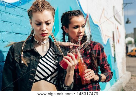Two Young Women Drinking Colorful Cocktails From Bottles