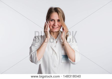 Young female doctor or nurse is shocked with hands on her mouth.
