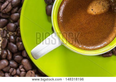 fresh bio espresso with a beautiful crema and strewn mediumly roasted coffee beans on burlap