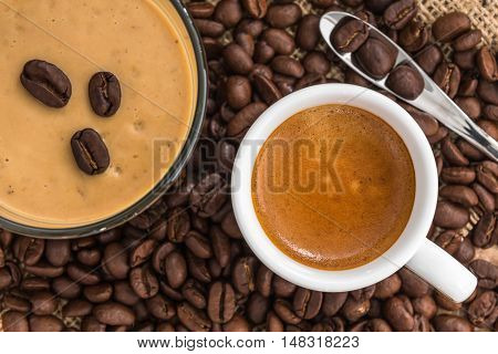 fresh espresso with a beautiful crema and coffee smoothie on strewn mediumly roasted coffee beans