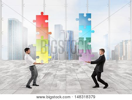 Businessmen hold a stack of puzzle fit together