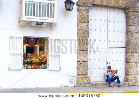 CARTAGENA COLOMBIA - MAY 25: Shop selling souvenirs and a man sitting on the sidewalk in Cartagena Colombia on May 25 2016