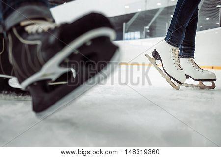 Man's hockey and women's figure skates on ice background.