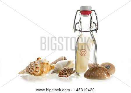 email message in a bottle made of glass between some sea shells isolated on a white background