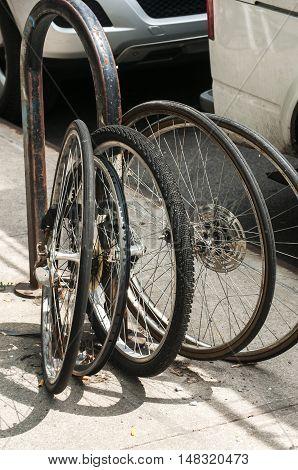 Used bicycle wheels locked to street pole