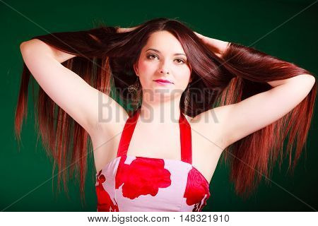 Hairdresser hairstylist and haircare. Long haired beauty woman creating coiffure. Studio shot on green background.