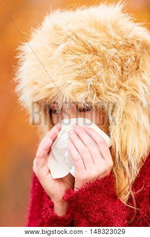 Sick Woman In Autumn Park Sneezing Into Tissue.