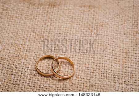 Two gold wedding rings lying on brown cloth sacking
