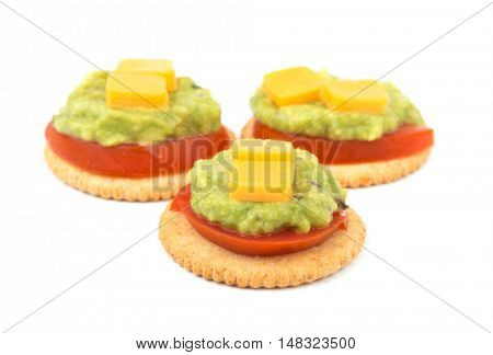 Whole grain crackers with tomato, guacamole and cheese on top, on white