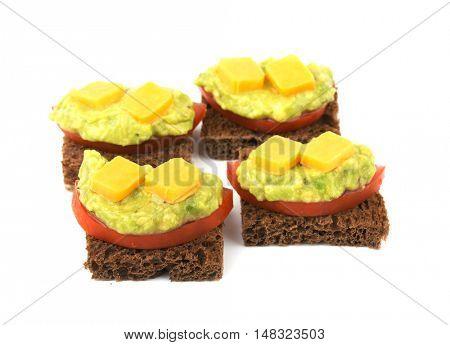 Dark sourdough rye bread slices with tomato, guacamole and cheese, on white