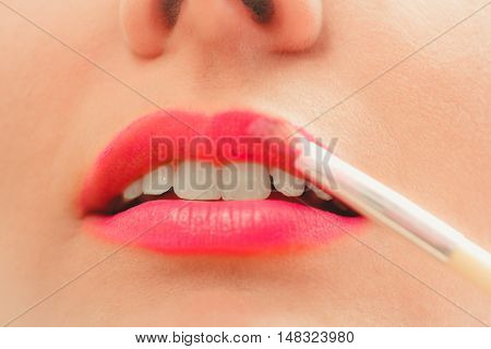 Close up of woman applying lipstick with brush on lips. Girl beautifying herself. Beauty and make up concept.