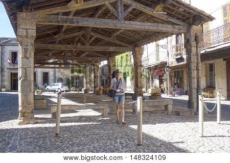 Photographer Walking Under A Porch In Lagrasse, France