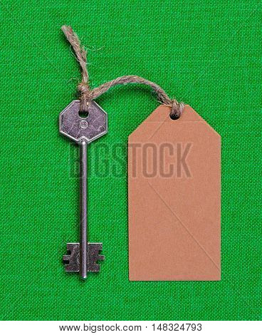 brown paper tag attached to the metal silver key on the green  fabric background
