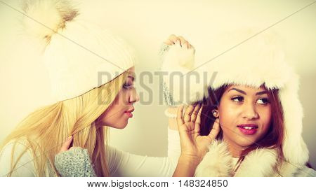 Clothing people fashion concept. Two ladies with winter outfit. Blonde woman together with mulatto girl wearing white warm clothes.