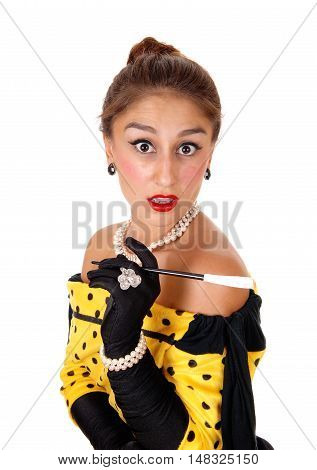 A beautiful young woman in a yellow dress and black gloves holding a cigarette isolated for white background.