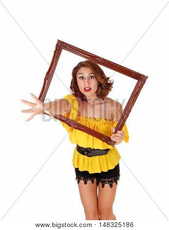 A angry woman in a yellow blouse and black shorts stretching her hand trough a picture frame isolated for white background.