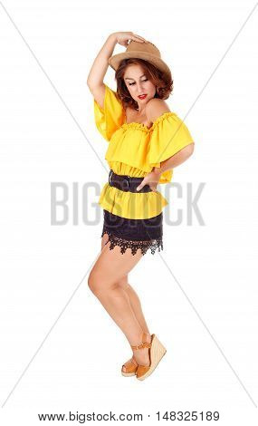 A lovely young woman posing in black shorts and yellow blouse with a cowboy hat isolated for white background.