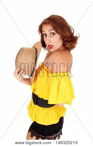 A beautiful woman in a yellow blouse and black shorts looking surprised into the camera standing isolated for white background.