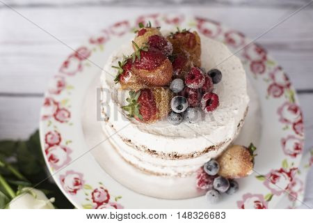 Naked Cake With Caramelized Fruits - Strawberries, Blueberries, Raspberries. Sponge Cream Cake In Fl