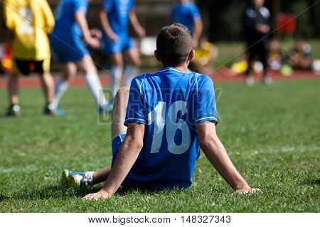 Player watching amateur soccer game