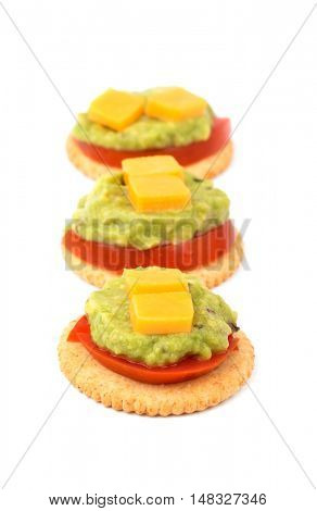 Whole grain crackers with tomato, guacamole and cheese lined up, on white