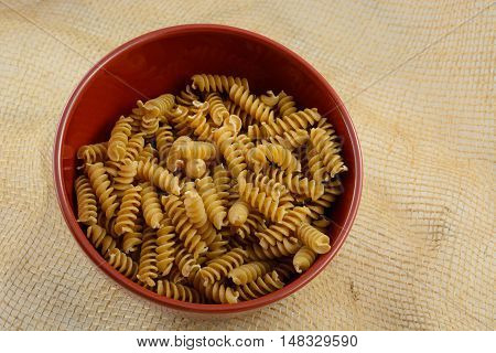Bowl of uncooked dry whole wheat pasta in red bowl on burlap