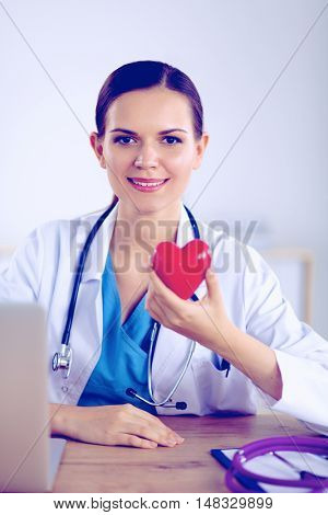 Young doctor with red heart symbol sitting at desk