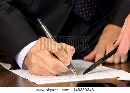 hands of business men and women studying the documents