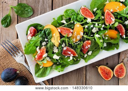 Autumn Salad Of Arugula, Spinach Figs And Goat Cheese In A White Rectangular Plate, Overhead Scene O