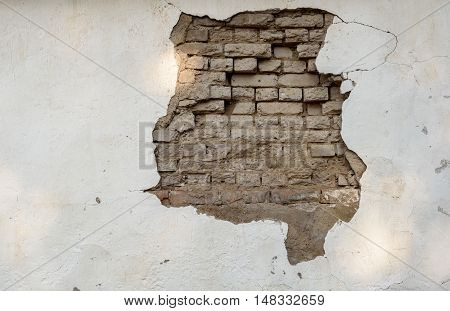 Crumbling Paintwork And Wall With Exposed Bricks